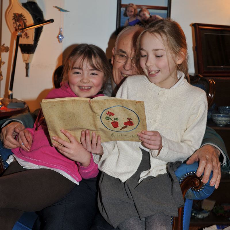 Image of Molly and Milly Shirley reading their Great Grandad's gardening diary with their Grandad, Jeremy.
